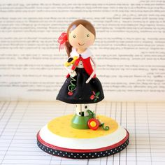 This bright and colorful Clothespin Doll is dressed in a Cherry Print skirt made from Mary Engelbreit fabric. Accessorized with a red jacket and dotty tights, and holding a single Sunflower bloom. Her medium brown hair is pulled up in a side pony tail and tied with a red bow.