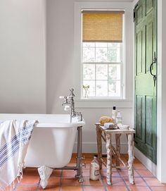 Handmade terra-cotta tiles and a claw-foot tub outfit the master bath in this Connecticut cottage. The circa-1780 door conceals a medicine cabinet and linen closet.   - CountryLiving.com
