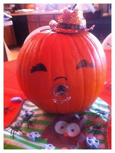 Halloween Baby Shower centerpiece. SUPER EASY! Fake pacifiers you purchase at Michael's in the baby shower section work better than real ones. Draw on eyes with marker. (Add eyelashes for a girl.). I used tooth picks to hold hat in place.