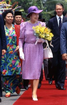 Pretty in purple on a trip to Malaysia in October 1989, The Queen looked the epitome of spring chic, in a flower adorned hat and yellow bouquet.