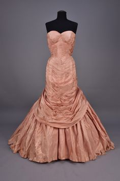 CHARLES JAMES STRAPLESS TREE BALLGOWN, c. 1952. Pink silk taffeta having boned, fitted sweetheart bodice with graceful double arc at back, covered in angled 1/2 inch pleats dipping into a front point at waist, interior satin corset, draped apron polonaise pleated at the reverse angle into outer back zipper forming a diamond at the waist over full skirt with six crinoline layers of rose pink to white, gathered at back for added volume over two semi-rigid under skirts.
