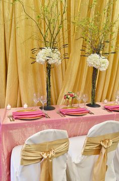 This event or wedding decor look uses gold draping, pink iridescent table linen, gold charger wrapped with pink napkins, white chairs with gold matte satin sash ties, and specialty votive trees. | FestivitiesMN.com