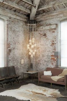 Faded, old exposed brick. High ceilings. Cowhide rug. Vintage stadium seats. Incandescent lighting.