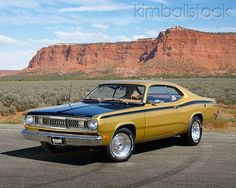 AUT 23 RK3456 01 - 1971 Plymouth Duster Gold With Black Stripes 3/4 Front View On Pavement In Desert - Kimballstock