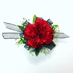 Single red carnation with baby's breath and black ribbon. Prom wrist corsage
