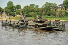 """U.S. Army M1A2 SEP V2 Abrams Main Battle Tanks, M2A3 Bradley Infantry Fighting Vehicles as well as various trucks and vehicles of Delta Company """"Dark Knights"""", 3rd Battalion, 69th Armor Regiment, 1st Armor Brigade Combat Team, 3rd U.S. Infantry Division conduct combined assault river crossing operations at the river Elbe with German Army M3 amphibious bridging vehicles during exercise Heidesturm Shock near Storkau, Germany, June 06, 2015. (U.S. Army photo by Visual Information Specialist…"""