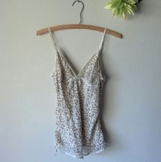 Abercrombie & Fitch Cami Abercrombie & Fitch camisole. Light brown and cream color flowery design. 100% silk. Cute button detail on one side and ties at bottom. Adjustable straps. Liner built in. Worn once! Great condition!! Sorry, no modeling. No trades.  Price FIRM unless bundled. Abercrombie & Fitch Tops Camisoles