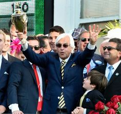 Trainer Bob Baffert holding The Preakness trophy