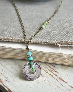Such a great every day necklace! Wear it alone or layered with others. Features a vintage coin,assorted glass beads, gemstone bead,rhinestone bead,antique brass chain. Necklace measures 24 and finishes with a lobster claw.