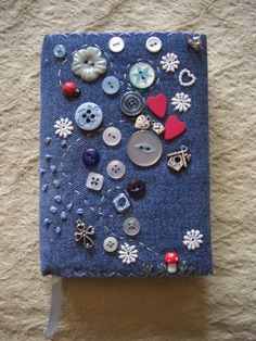 Handmade General Craft Item £7.50. A gift idea by Karen Smith found on www.MyOwnCreation.co.uk: A lovely little fabric covered address book.  The book is padded and covered in blue denim, hand sewn, decorated with buttons, Tibetan silver charms, embroidered French knots and a tiny wooden toadstool and ladybird.  The back of the book features a small fairy panel and rustic embroidered Handmade with Love.  A single name could be embroidered on the front of the book if required.