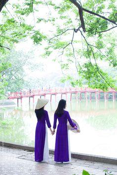 Two Vietnamese women standing infront of Ho Kiem Lake,, Hanoi. by Hugh Sitton - Stocksy United Vietnamese Traditional Dress, Vietnamese Dress, Stock Imagery, Hanoi Vietnam, Woman Standing, Bridesmaid Dresses, Wedding Dresses, Ao Dai, The Unit