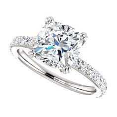 A stunning 2.5 carat cushion cut Forever Brilliant moissanite is hand set in a diamond-studded white gold setting. Moissanite is an amazing gem