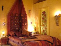indian ethnic interior design. Maroon canopy for the bed. Warm yellow walls and indirect lighting.