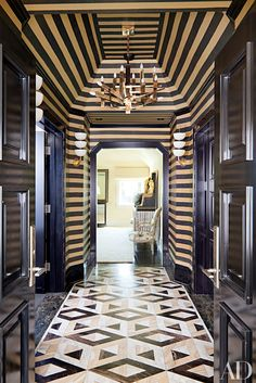 Part of the master suite in this Bel-Air home decorated by Kelly Wearstler, this striped vestibule is accented by an Italian modernist chandelier and vintage sconces. Read on for more beautiful hallways by AD100 honorees.