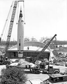 """Construction of the original TWA Moonliner at Disneyland's Tomorrowland """"Rocket to the Moon"""" attraction (1955). Note the rocket's support struts still on the flatbed."""