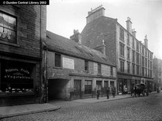 """Hawkhill, Dundee - Ref: WC0193 This section of the Hawkhill in Dundee (which led westwards from West Port to Perth Road) shows the archway into Isles Lane. To the west (and left) of the arch is Charles Laing's fruit shop. The building to the right has an advertisement for Woodward's """"fish suppers""""; John Woodward sold fish at No. 110a Hawkhill. At No. 115 Hawkhill (to the right of the photograph) is one of the City of Dundee Co-operative Society's five general stores."""