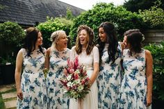 Bridesmaids wear blue floral dresses for a rustic Dorset barn wedding with paper cranes. Photography by Richard Skins.