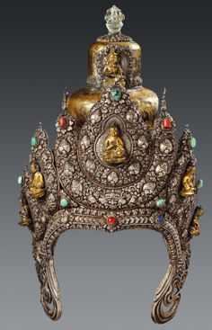 """An eastern Tibetan copper and silver repoussé vajrasrattva headdress of conical form with three rounded tiers separated by foliate bands. The attached silver repoussé tiara depicting five copper Jina Buddhas in relief with aureoles, including Vajrasattiva within a niche at the top, surrounded by a rock-crystal vajra finial. c. 1900 or earlier."""