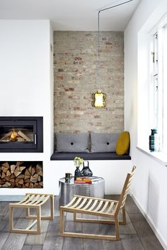 Wood burner with feature exposed brick wall and seating. White, brick, grey, black.