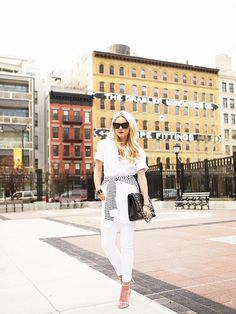 Atlantic Pacific / white button-down shirt, white skinny jeans, white sandals, a striped sweater around the waist, a Chanel bag, and cat-eye sunglasses