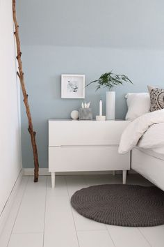 Schlafzimmer: hellblaue Wand mit weißen Möbeln.