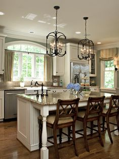 Traditional kitchen with painted white cabinetry, beautiful granite tops, stainless steel appliances, huge window with arched transom above sink and an amazing large island with prep sink and unique candelabra-style pendant lighting.  **GORGEOUS!!!!** love this but I want white appliances