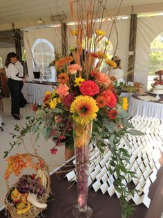 Gorgeous fall centerpieces of gerbers, roses, sunflowers, mums, wheat and grapevine in tall glass vases with grapes in them for a winery reception. Designed by Jen-Mor Florist in Dover, DE. www.jenmor.com