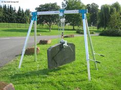 A 500kg capacity Mini Gantry Crane & Screw Clamp lifting stone on an uneven grassy ground.