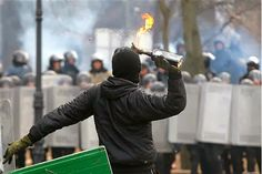 A protester throws a Molotov cocktail during unrest in central Kiev, Ukraine, Monday, Jan. 20, 2014. After a night of vicious street battles...