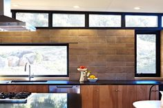 Bronze anodized window frames, black Cesarstone countertops, natural birch cabinets and Watershed Blocks. Lighted from above as they are here, the color variations in each individual  rammed earth block  reveal the minerality of their composition.  Image © Jacob Snavely