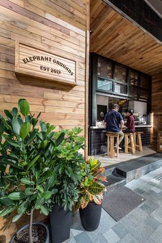This cafe has a simple color palette of wood, white and black, with a touch of green from the plants.