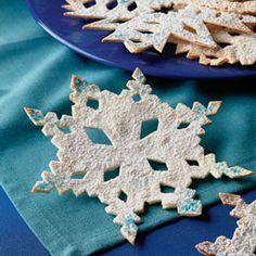 Edible Snowflakes - Warm tortillas in oven to soften, fold in half, then half again, cut designs into edges, unfold.  Bake in 400 degree oven until lightly browned and crisp. Sift confectioners sugar on snowflakes while still warm. (I can't imagine using edible glitter as suggested, but I think they'd be really good with cinnamon sugar on them!)