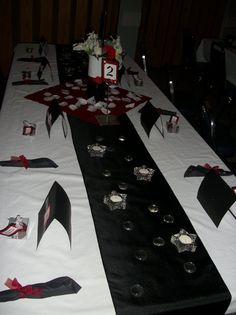 red, black and white wedding setting. napkins rolled with black napkins and tied with red ribbon, black runner with clear gems and star tea-light holders, scrap-paper table numbers and programs, and home-made enterpieces