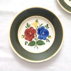 2 assiettes de Villeroy et Boch en point fantaisie Bauernblume. années 1980.  Une plaque sandwich ou déjeuner est 9,75.  Une assiette de salade ou dessert est 8 5/8.  Peint à la main à Mettlach en Allemagne. Folk art design se marie bien avec un décor modern ou traditionnels.  Fleurs rouges et bleus foncé avec des accents jaunes et vertes sur la plaque de déjeuner. Une fleur rouge sombre sur lassiette de salade.  Les deux modèles ont frontières de la bande verte et jaune et dentelées…