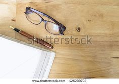 Copyspace of topview of wooden working desktop in office. Glasses, pen and empty white book page.