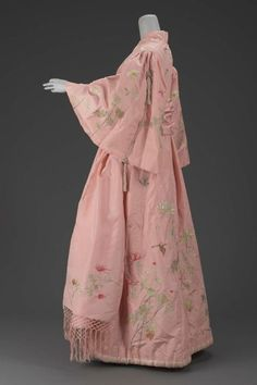 """Dressing Gown Iida Takashimaya, 1900 The Museum of Fine Arts, Boston: ""Pink silk taffeta dressing gown in kimono style with embroidered naturalistic chrysanthemums and butterflies in polychrome silks. Silk plain weave lining, padded hem and pleat in back of robe. Full sleeves gathered at shoulders and trimmed with braided silk cord and tassles. Matching sash of pink silk taffeta with double-sided embroidery of chrysanthemums in green brown and pink polychrome silk with knotted silk fringe…"