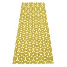 Das an Honigwaben erinnernde, grafische Muster dieses Teppichs ist neben dem hier präsentierten Modell in der Farbstellung senfgelb-vanille auch in anderen Farbtönen erhältlich. Ein hochqualitativer Pappelina-Teppich Made in Sweden!