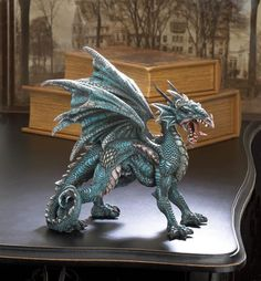 Add some fierce style to your bookshelf or desk with this fantastical dragon statue. This finely detailed beast stands on all four with wings spread, and is captured mid-roar. Material(s):POLYRESIN We