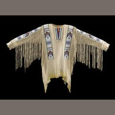 Sioux beaded shirt - A two-hide poncho-style garment, fringe about the sides and down the sleeves, applied strips of beadwork across the shoulders and along the arms, remains of red trade cloth at the neck, yellow dye on the lower hem.