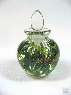 "Glass Designer/Maker:  Steven Lundberg Markings:  Engraved ""Steven Lundberg 99"" on lower side Origin:  California Date or Era:  1999 Dimensions:  3.75 in. Additional Information:  Hand blown clear glass with black and gold butterfly, green leaves and fronds. Clear teardrop stopper."