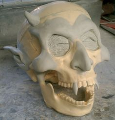 add clay 'features' to a skull. paper mache or corpse in skin. paint.