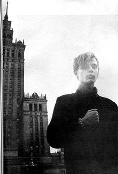 Robert Brylewski of Polish post-punk group Brygada Kryzys (The Crisis Brigade) standing in front of one of the major achievements of Stalinist architecture, The Palace of Culture and Science in Warsaw. Poland (ca. 1982)