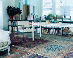piles of Persian carpets and bookshelves