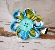 """Petite Fleur"" is a small blue and green patterned fabric cherry blossom style kanzashi flower with blue button center. The cherry blossom flower is secured to an alligator clip for wear in your hair, clipped to your lapel, headband, purse or more. #handmade #gift #flower"