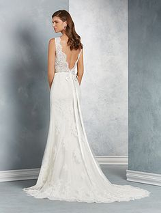 A classic wedding gown with a V-shaped neckline, sheer shoulder straps, natural waist, flared skirt, and chapel train.