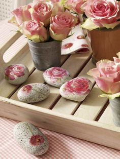 Rocks with Flowers - cut out a flower pattern from a napkin, remove the thin top layer of the napkin, glue to the stone with napkin glue, let dry and then add one more layer of glue on top.