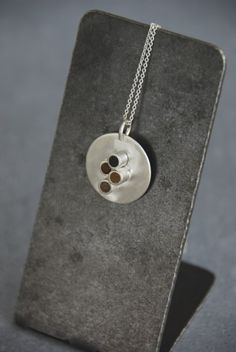 Spice Tube Pendant: Resin spiked with spices fill the tubes decorating this sterling silver disc pendant.