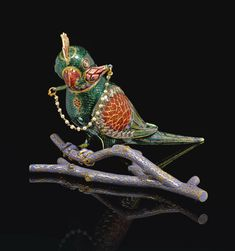 A gold, polychrome enamelled and gem-set parrot-form flask (chuski) on a branch. North India, 19th century, the parrot perched on a lavender-coloured forked branch, decorated with translucent emerald green and red enamel on a chased feather-like chevron ground, with faceted gem-set collar and border around wings, a lotus blossom in its beak and seed-pearl chain stopper, with crest-form screw-on cover