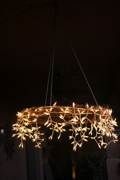 DIY Chandelier using a grape vine wreath. I would do with regular strings of lights and not icicles.