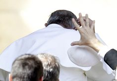 A member of security tries to grab Pope Francis skullcap after it was blown by a gust of wind at the end of the weekly audience in Saint Peters Square at the Vatican.